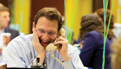 Man grins as he talks on the phone